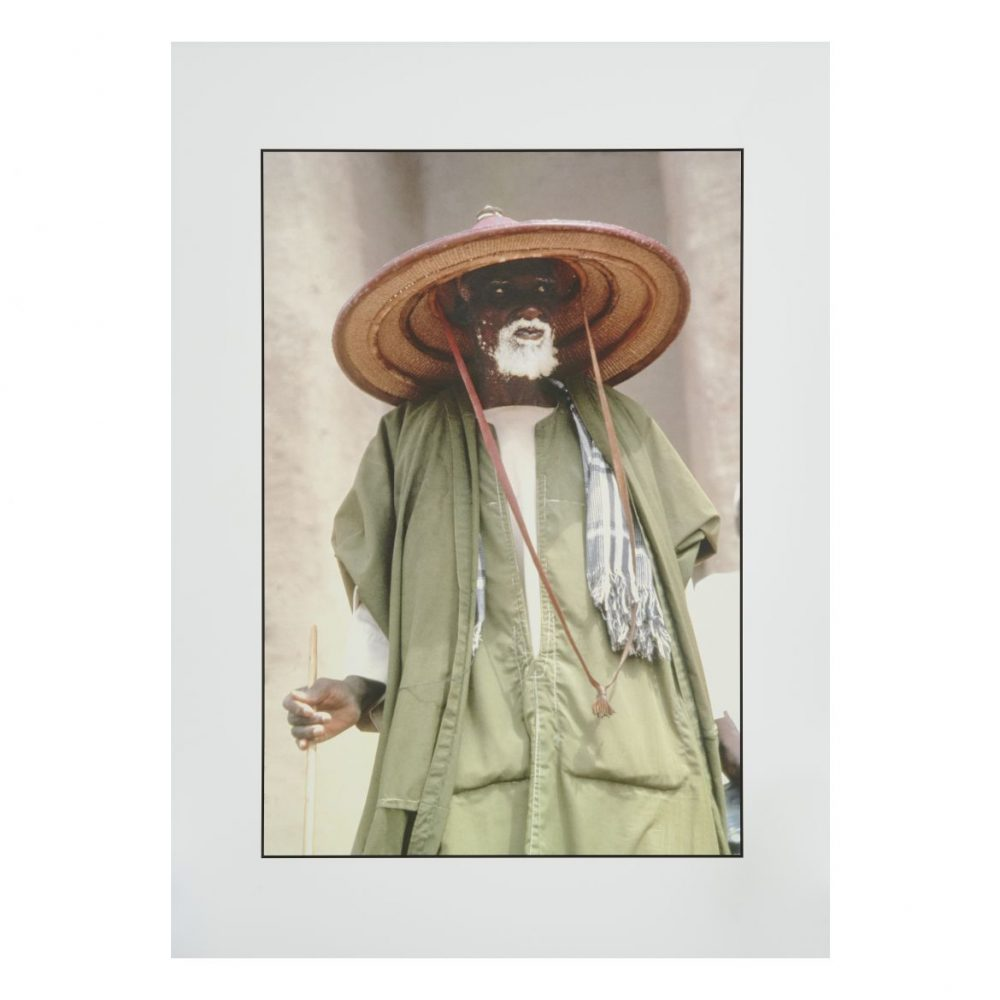 Mirella Ricciardi Elder Wearing a Fulani Straw Hat & Green Robe at Market